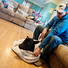 Globe/Roger Nomer<br /> Traves Merrick wraps up a newborn calf in his living room in Miller on Wednesday. During the record cold weather, the Merricks have brought calves inside to warm up, including this one born early Wednesday morning.