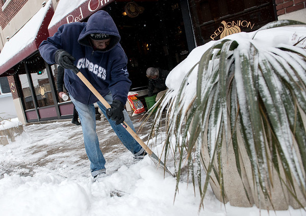 Globe/Roger Nomer<br /> Don Brooks clears the walk outside the Red Onion Cafe on Monday morning.