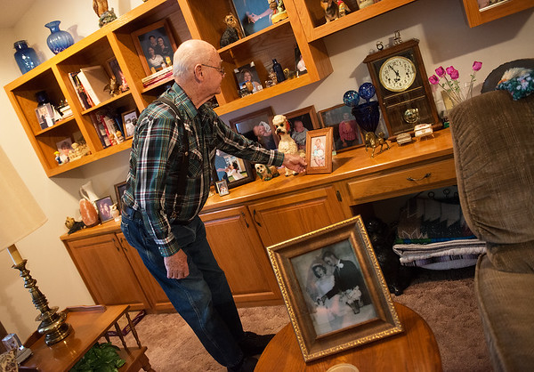 Bob Fields looks over family photos in his home on Wednesday in Neosho.<br /> Globe | Roger Nomer