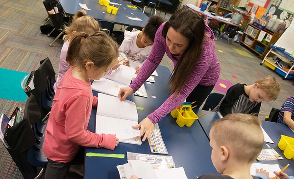 Melissa Miller helps her kindergarten students with their handwriting journals on Thursday at Cecil Floyd.<br /> Globe | Roger Nomer