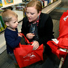 Joplin Public Library Children's Assistant Becee McNally assists Hudson Jarrett, 2, as he becomes the first to check out a bag of five books for the 1,000 Books Before Kindergarten program, which kicked off Friday at the Joplin Public Library.<br /> Globe | Laurie Sisk