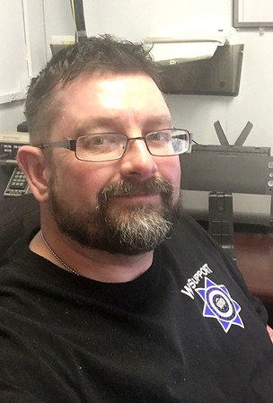 Baxter Springs Police Officer Jimmy Hamilton sits at the police department's dispatch desk on Friday. Hamilton was recently medically cleared to return to light duty and his official first day back was on Monday.  Courtesy Photo/JoplinGlobe