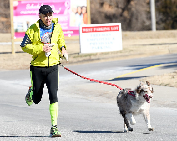 "Sixty four-year-old Henri Coeme and his running partner ""Miles"" capture first place in the Joplin Family YMCA's Chilly 5k on Monday morning at the YMCA. Ninety four runners braved frigid temperatures to run the annual New Year's Day race.<br /> Globe 