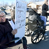 Seventy four-year-old Zenith Emory joins protestors across from Lozier Corporation as Missouri Governor Eric Greitens talks about his tax plan for the state on Tuesday afternoon.<br /> Globe | Laurie Sisk