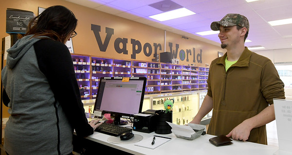 From the left: Vapor Maven Sales Associate Samantha Hardcastle assists customer Robert Hayes on Friday.<br /> Globe | Laurie Sisk