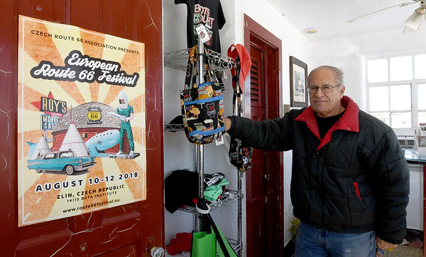 The Route 66 Chamber of Commerce Director and founder, Rod Harsh, stands next to a promotional sign for a Route 66 festival in Czechoslovakia on a wall in the lobby of Boots Court in Carthage on Thursday.<br /> Globe | Laurie Sisk