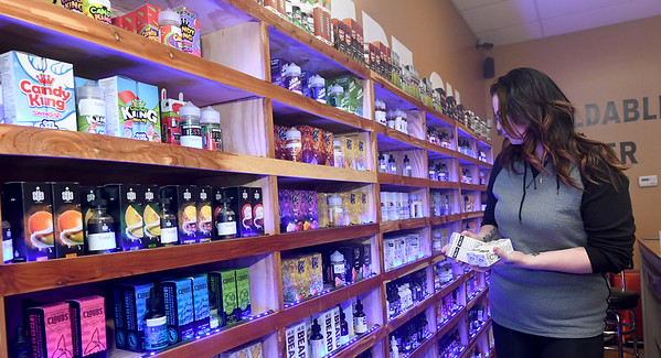 Vapor Maven Sales Associate Samantha Hardcastle restocks shelves at the store on Friday.<br /> Globe | Laurie Sisk