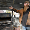 Westside BBQ owner Carl Wiest talks about the recent fire that closed his business as he stands among the charred remains of a smoker at his popular restaurant on Tuesday. Wiest is unceratin when he and his wife, Julie Wiest, will be able to reopen.<br /> Globe | Laurie Sisk