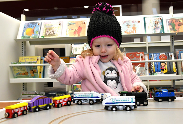 Three-year-old Eleanor Adcock escapes the chilly temperatures outside as she plays with a train set on Thursday afternoon at the Joplin Public Library.<br /> Globe | Laurie Sisk