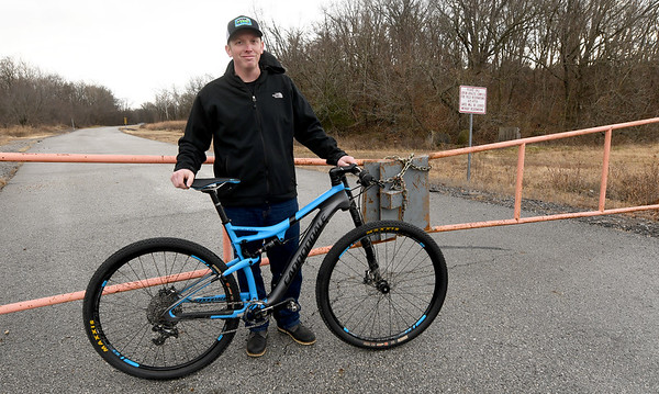 Blue's Bikes owner Mark Cox stands near a plocked gate to the seldom used Dover Park.  Cox is forming a non-profit organization to help give life to the park.<br /> Globe | Laurie Sisk