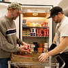 Gary Brown, left, and Michael Bartlett stock food donations at Crosslines on Friday.<br /> Globe | Roger Nomer
