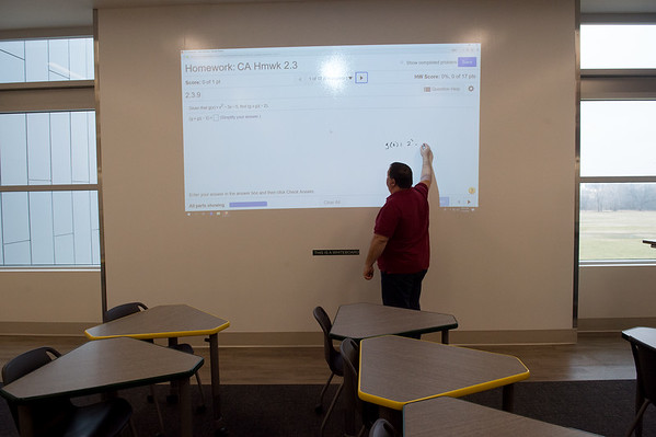 Kerry Johnson, department head of mathematics at Missouri Southern, demonstrates a new whiteboard in a classroom at Nixon Hall on Tuesday.<br /> Globe | Roger Nomer