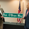 Toby Teeter, president of the Joplin Area Chamber of Commerce, right, presents Rob O'Brian, former Chamber president, with a sign that will rename a street in the Crossroads Industrial Park after him during a reception on Thursday at the Chamber. The reception honored O'Brian for his 23 years of service to the Chamber and the City of Joplin.