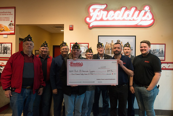 (from left) American Legion Post 13 members Larry Cagle, Bill Herford, Sam Mahurin, Tod Thompson, Jim Dunn, Warren Turner and Kavan Stull accept a check for $487 from Brandon Logan, district manager of Freddy's Frozen Custard and Steakburgers, and Hunter Maki, assistant general manager, right, on Friday at the restaurant in Joplin. Freddy's collected the money through last year from a donation box at the counter.<br /> Globe | Roger Nomer