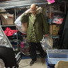 Dean Barnes helps sort warm clothing at Watered Gardens on Tuesday afternoon.<br /> Globe | Roger Nomer