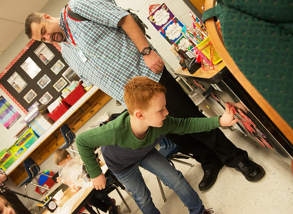 Jackson Moore helps David Meinershagen with classroom chores on Wednesday at Webster Elementary in Webb City.<br /> Globe | Roger Nomer