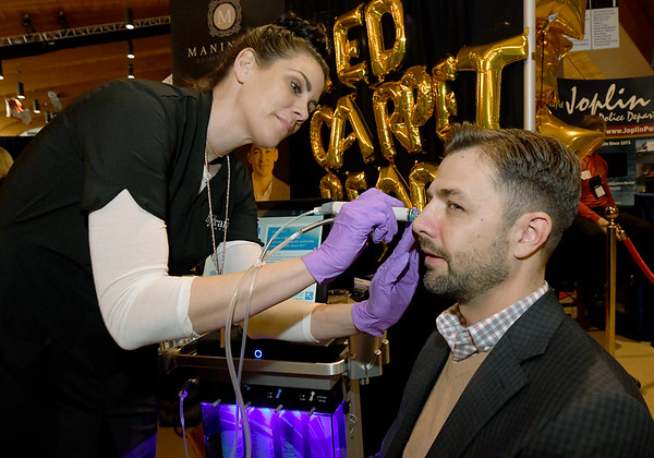 """Jen Tegethoff, of HydraFacial, treats Lance Clevenger to a """"spring cleaning for the skin"""" at the Maningas Cosmetic Surgery booth during the 26th Annual Joplin Area Chamber of Commerce Business EXPO at Downstream Casino on Tuesday.<br /> Globe 
