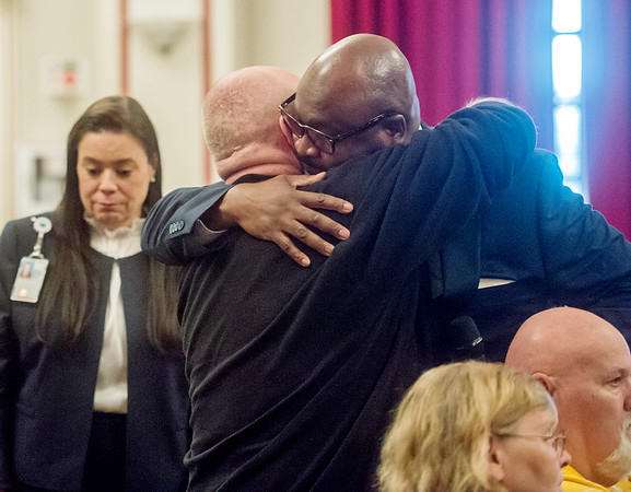 Kelvin Parks, director of Veterans Health Care System of the Ozarks, gives a hug to Tim Lybyer, Fayetteville, during a town hall meeting on Monday in Fayetteville. Lybyer recounted the death of his brother to Parks and suspects his brother might have been seen by a discredited pathologist at the clinic.<br /> Globe | Roger Nomer
