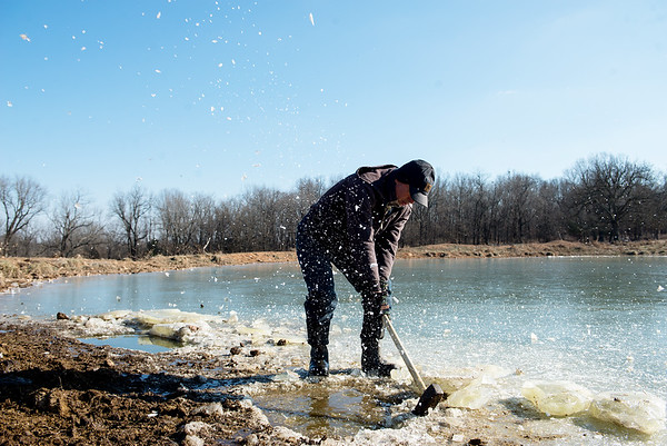 Globe/Roger Nomer<br /> Russell Marion cuts a hole in a frozen pond for his cattle on Wednesday near Pierce City.