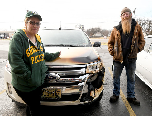 Julie and Carl Wiest, owners of Westside BBQ, stand near their vehicle, which was heavily damaged in a fire at their popular restaurant.<br /> Globe | Laurie Sisk