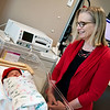 Globe/Roger Nomer<br /> Peggy Scott, communications coordinator for the American Heart Association, checks in on Margaret Brennfoerder, born early Tuesday, at Mercy Hospital on Tuesday. Brennfoerder was one of the first newborns to receive a red knitted cap from the American Heart Association in honor of February being American Heart Month. Volunteers knitted the hats to be distributed to newborns born at area hospitals to inspire families to lead heart healthy lives and promote awareness about congenital heart defects.