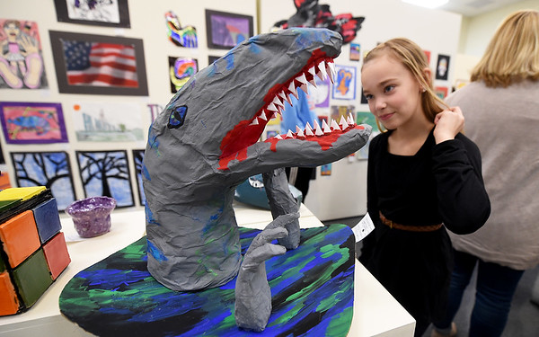 """Ten-year-old Adelaide Davidson, of Webb City, checks out  """"Papier Maché Dino,"""" created by McDonald County seventh graders Katie Teed and Kaitlyn Mustain. The piece was one of scores on display during the recepton for the 8th Annual K12 Art Show at Missouri Southern's Spiva Art Gallery on Saturday. The exhibit runs through Jan. 18 at Spiva.<br /> Globe 