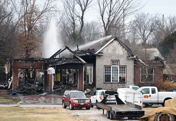 Carl Junction firefighters work to extinguish the remaining embers at a house fire near Wells Street and County Lane 287 on Thursday afternoon in Carl Junction.<br /> Globe | Laurie Sisk