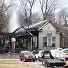 Carl Junction firefighters work to extinguish the remaining embers at a house fire near Wells Street and County Lane 287 on Thursday afternoon in Carl Junction.<br /> Globe   Laurie Sisk