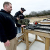 From the left: Jason Lankford, customer service and technical manager at Black Rain Ordinance, and Black Rain gunmaker Jeremy Preston prepare to fire weapons on the test range at Black Rain Ordnance on Thursday. The company has grown from a small business to a company that sells about 10,000 guns a year and will celebrate its 10th anniversary on Tuesday.<br /> Globe | Laurie Sisk