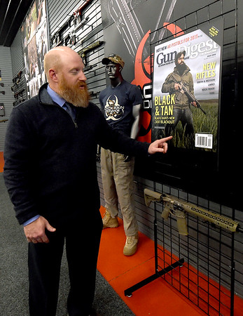 Black Rain Ordnance President Justin Harvel stands near one of several reproductions of publications which have featured the Neosho business over the past 10 years. Rifles line the walls of Black Rain Ordnance on Thursday. The company has grown from a small business to a company that sells about 10,000 guns a year and will celebrate its 10th anniversary on Tuesday.<br /> Globe   Laurie Sisk