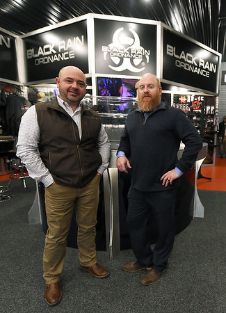 From the left: Black Rain Ordnance Vice President Charlie Spires and President Justin Harvel stand inside their store on Thursday. The company has grown from a small business to a company that sells about 10,000 guns a year and will celebrate its 10th anniversary on Tuesday.<br /> Globe | Laurie Sisk