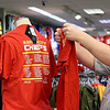 From the left: Nick Shelton and Tayton Majors, both of Fort Scott, check out the Chiefs divisional championship shirts at Pro Image Sports at Northpark Mall on Wednesday. Chiefs fans are preparing for Kansas City's play off matchup against the Indianapolis Colts on Saturday afternoon.<br /> Globe | Laurie Sisk
