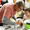 From the left: Missouri Master Naturalist Val Frankoski, of the Chert Glades Master Naturalists, assists 5-year-old Madison Clemons in making a seed bomb of wildflowers during the Pollinator Seed Bomb Workshop for Kids on Saturday at Empire Market. The event featured an educational presentation on pollination and hands-on experience in making seed bombs.<br /> Globe | Laurie Sisk