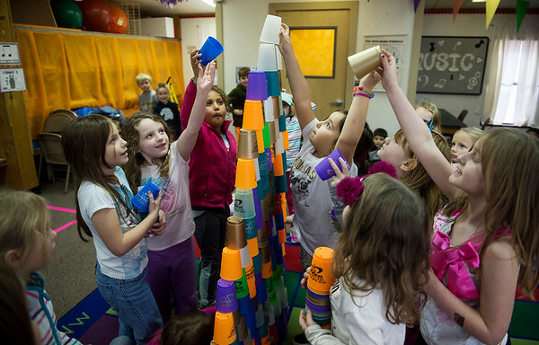 A kindergarten physical education class stacks cups on Jan. 30 at Columbia Elementary. With the school's gymanisium closed, physical education class has to be held in hallways and the music room.<br /> Globe | Roger Nomer