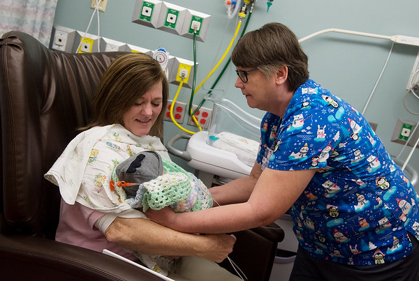Sarah Wall, a cuddler at Freeman Hospital, hands off Lucas Wooten, 4 days, to Bonnie Sutherland, a registered nurse in the NICU, at the Freeman NICU on Tuesday.<br /> Globe | Roger Nomer