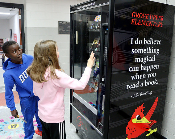 """Kangwa Cloud reacts as Allison Case uses her token to """"purchase"""" a book from the Grove Upper Elementary Book Worm Vending Machine. Students can earn tokens for a variety of reasons, which lets them pick out a book as a reward. <br /> Globe 