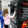 "Kangwa Cloud reacts as Allison Case uses her token to ""purchase"" a book from the Grove Upper Elementary Book Worm Vending Machine. Students can earn tokens for a variety of reasons, which lets them pick out a book as a reward. <br /> Globe 