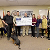 "Jasper County Sheriff Randee Kaiser and Arvest Commecial Loan Manager Ray Tubaugh, center, hold a check for $10.000 for the JCSO's body cam and dash cam project on Wednesday at the sheriff's office in Carthage. The duo are joined by representatives of the JCSO, Arvest and JCSO tracking dog ""Skye."""