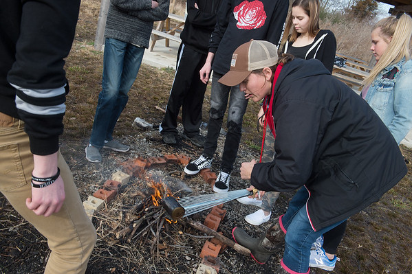 Chelsi Leggett shows her students how to make a char cloth at the Carl Junction outdoor classroom on Tuesday.<br /> Globe | Roger Nomer