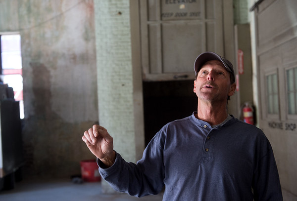 Tony Anderson talks about the ceiling construction of the former Lewis Motor Company building on Joplin Street while working on Tuesday.<br /> Globe | Roger Nomer