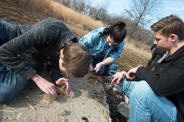 (from left) Marshall Samford, Carl Junction sophomore, Emme Beaver and Clay Sneed, juniors, work on making fires at the Carl Junction outdoor classroom on Tuesday.<br /> Globe | Roger Nomer