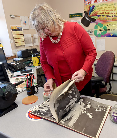 Joplin Recycling Center Director Mary Ann Phillips leafs through an Associated Press book on the Kennedy assassination - one of her favorite finds - on Tuesday at the center. <br /> Globe | Laurie Sisk