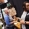 Linda English (left), with Forget Me Not Fleamarket, shows Shannon Barstow, sales manager with Towne Suites Plaza, a craft by Outback Creations on Tuesday at the Joplin Area Chamber of Commerce Business Expo at Downstream Casino.<br /> Globe | Roger Nomer