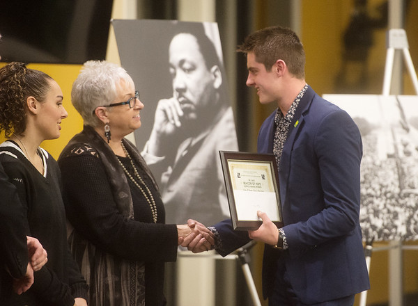 Byron Stevens, a Missouri Southern junior from Jasper and president of Delta Pi Chapter Kappa Alpha Order, accepts the Dr. Cade Beacon of Hope Service Award from Jalynn Smith-Ward (left), granddaughter of Al Cade, and Dorothy Cade, wife, on behalf of the organization during Monday's Dr. Martin Luther King Jr. Day Celebration at Missouri Southern.<br /> Globe | Roger Nomer