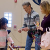 Constantinah Nguyen, first grader at Jefferson Elementary, sells Don and Laurel Gafken a paper wallet on Monday at Jefferson Elementary. First graders created paper crafts and then sold them to parents and the community as part of a lesson in economics. The students donated the proceeds from their crafts to Meals on Wheels.<br /> Globe | Roger Nomer