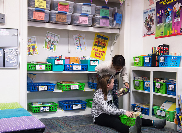 Bailee Johnson (left) and Molina Ross look through books in their second-grade classroom at West Central Elementary on Jan. 30. With little storage space at the school, teachers have to be creative about storing books for their libraries.<br /> Globe | Roger Nomer