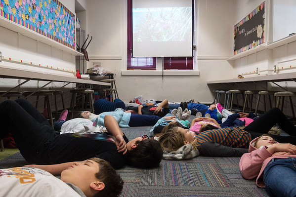 Fifth graders practice guided meditation on the floor of the counelor's classroom at Columbia Elementary. Small classrooms like these lead to overcrowding at the school.<br /> Globe | Roger Nomer