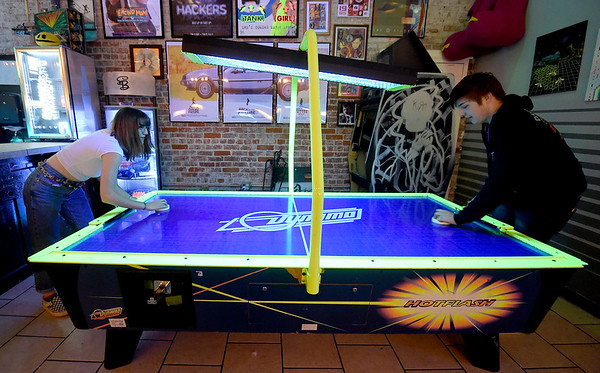From the left: Katelyn Pursley and Tyler Leach take in a game of Air Hockey during their first visit to Flicker.<br /> Globe | Laurie SIsk