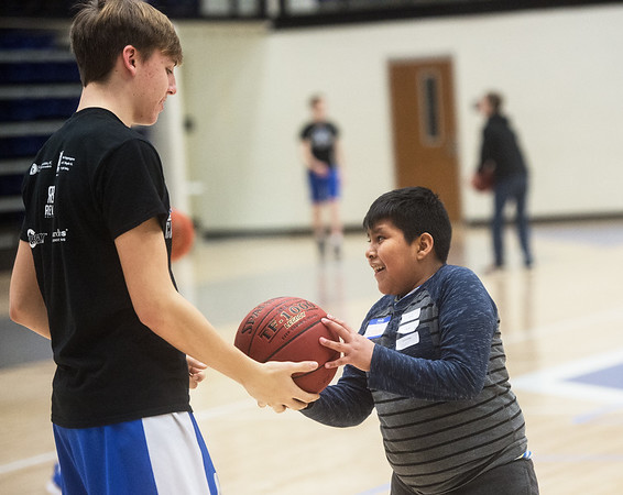 Zack Roberts, freshman at Carthage High School, helps Esteven Tema-Merida, fifth grader at Carthage Intermediate Center, with a shooting drill on Thursday at Carthage High School.<br /> Globe | Roger Nomer
