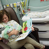 Sarah Wall, a cuddler at Freeman Hospital, reads to Lucas Wooten, 4 days, in the Freeman NICU on Tuesday.<br /> Globe | Roger Nomer